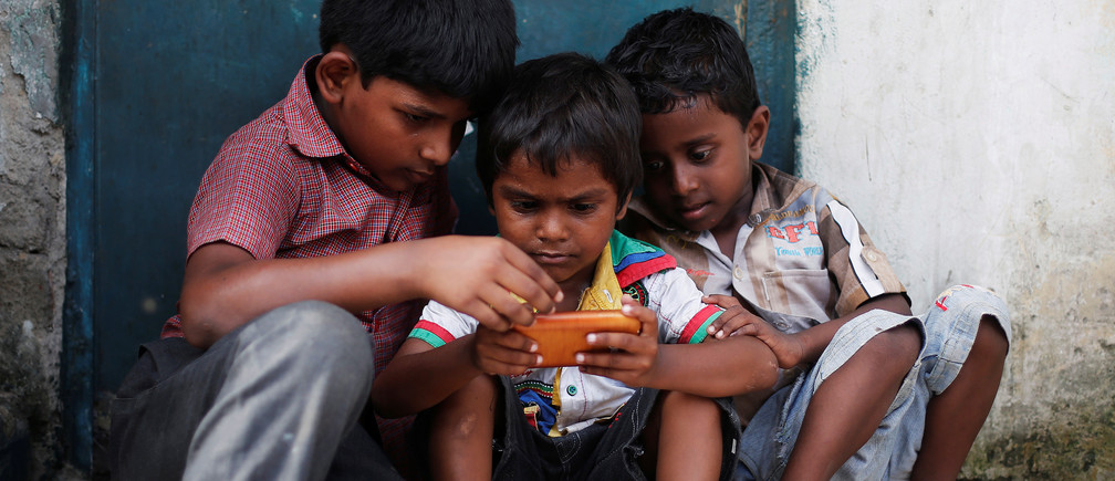 Children play on a mobile phone in New Delhi, July 2017