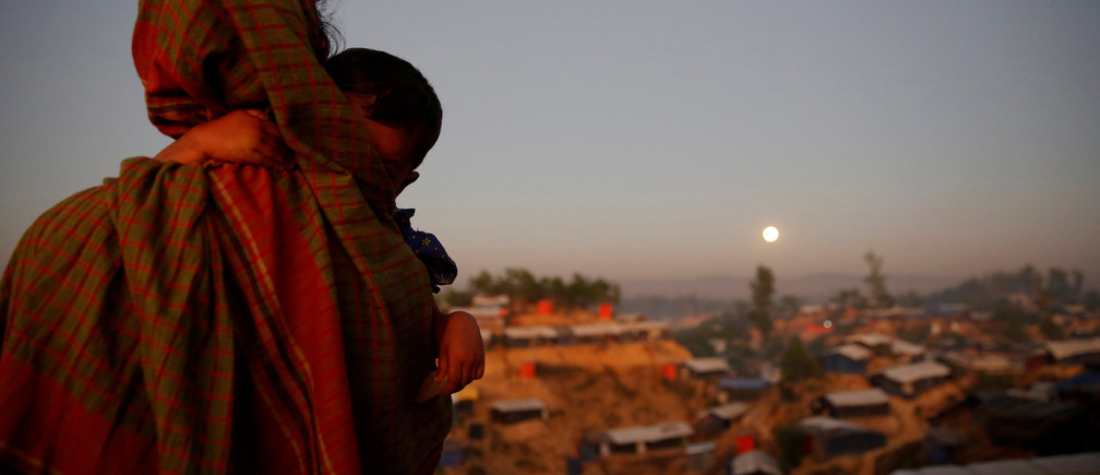 A Rohingya refugee looks at the full moon with a child in tow at Balukhali refugee camp near Cox's Bazar, Bangladesh, December 3, 2017.