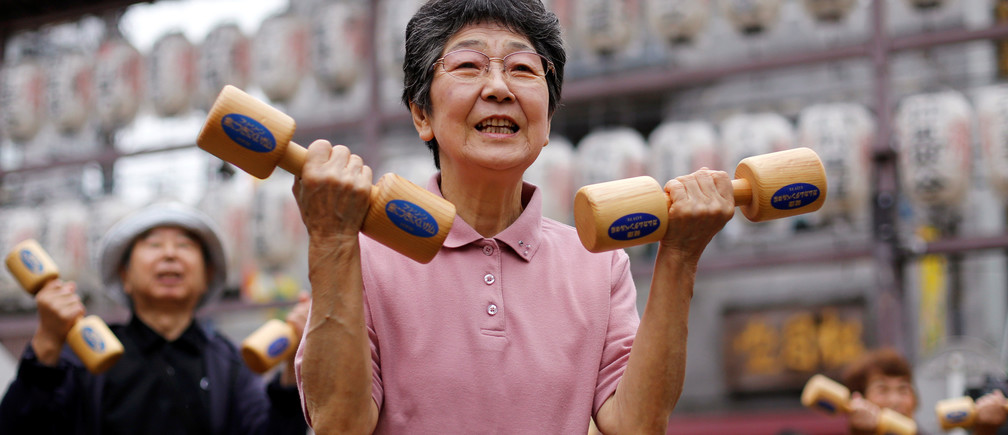 """Elderly and middle-aged people exercise with wooden dumbbells during a health promotion event to mark Japan's """"Respect for the Aged Day"""" at a temple in Tokyo's Sugamo district, an area popular among the Japanese elderly, Japan, September 19, 2016.    REUTERS/Toru Hanai - S1BEUCCVMXAA"""