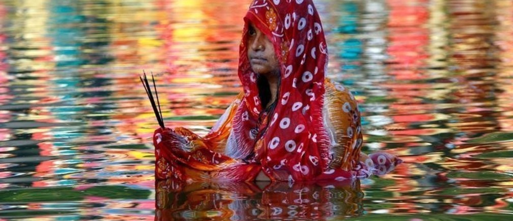 A Hindu woman worships the Sun god in the waters of a lake during the religious festival of Chhath Puja in Agartala, India, November 13, 2018. REUTERS/Jayanta Dey     TPX IMAGES OF THE DAY - RC1843E16EC0