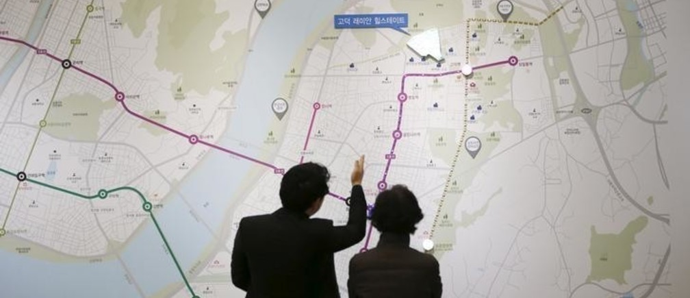 A salesperson (L) talks with a visitor in front of a map showing the location of an apartment complex which is currently under construction at its showroom in Seoul March 18, 2015. While activity is soaring, with the number of transactions at a 7-year high, housing prices are rising at a glacial pace as heavy household debt and a fast-ageing population keep a lid on price growth. To match story SOUTHKOREA-ECONOMY/HOUSING Picture taken on March 18. REUTERS/Kim Hong-Ji