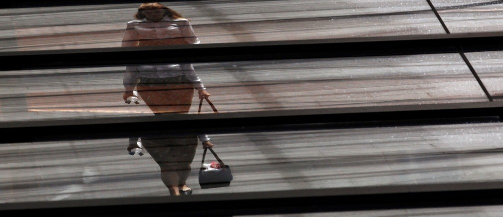 Image: An office worker is reflected on the roof of a building.