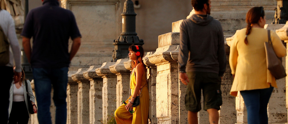 A woman wearing headphones stands on the Ponte Sant'Angelo bridge during sunset, amid the coronavirus disease (COVID-19) outbreak, in Rome, Italy, May 8, 2020. REUTERS/Guglielmo Mangiapane - RC2IKG9ZPX39