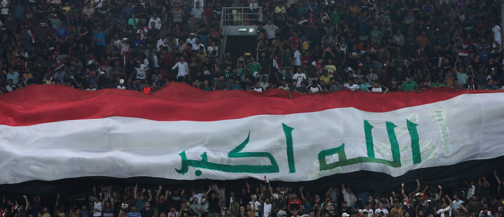 A Iraqi flag is held by fans during the game of the West Asia Football Federation Championship between Iraq and Lebanon at Kerbala Stadium in the holy city of Kerbala, Iraq July 30, 2019.Picture taken July 30, 2019. REUTERS/Abdullah Dhiaa Al-Deen - RC1F3EEE2E10