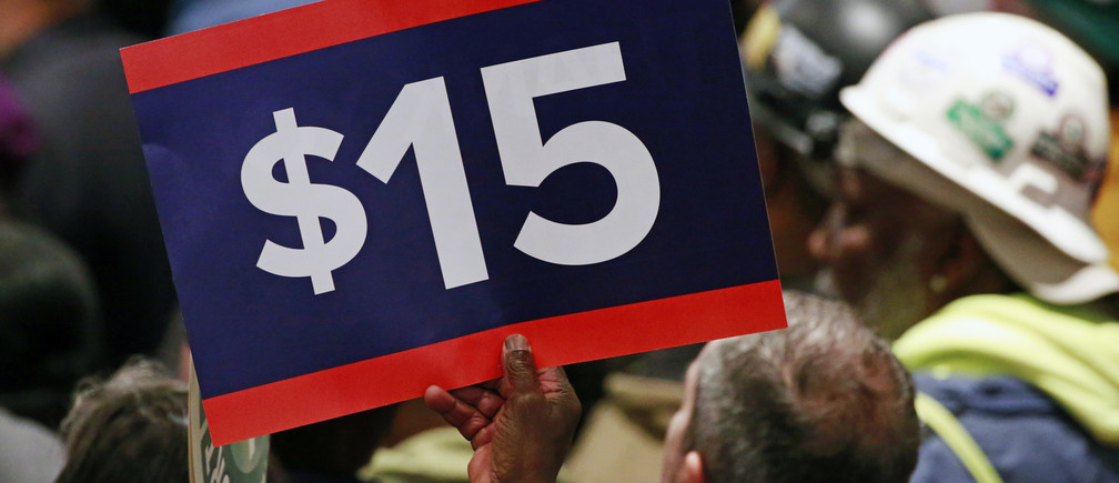 A supporter holds a sign aloft while listening to U.S. Democratic presidential candidate Hillary Clinton during a rally to celebrate the state of New York passing into law a $15 minimum wage in New York April 4, 2016.  REUTERS/Lucas Jackson - D1AESWLZGRAA