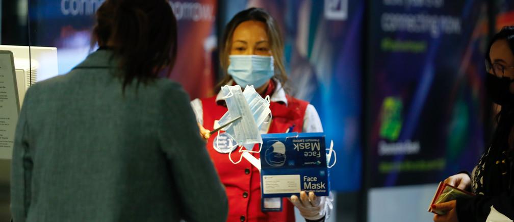 Un miembro del personal de control de pasajeros, reparte máscaras protectoras mientras el aeropuerto internacional presenta medidas de seguridad adicionales para COVID-19, en medio del brote de la enfermedad coronavirus en Frankfurt, Alemania, el 12 de mayo de 2020.