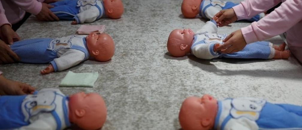 Students at Ayi University, a training program for domestic helpers, practice on baby dolls during a course teaching childcare in Beijing, China December 5, 2018. The training program teaches childcare, early education, housekeeping and other skills for domestic workers and is designed to meet the demand of China's middle class after the country scrapped the one-child policy. Picture taken December 5, 2018.  REUTERS/Thomas Peter - RC1B1810F8A0