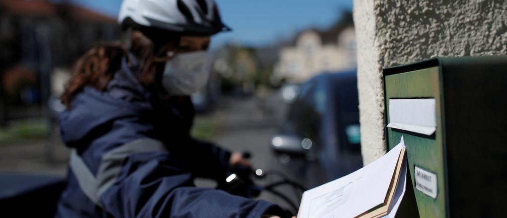 An employee of French postal service company La Poste wears a protective face mask out on delivery in Nantes.