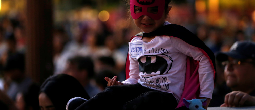 A young girl wears a costume before a bat-signal is projected on City Hall in honor of late actor Adam West in Los Angeles, California, U.S., June 15, 2017.   REUTERS/Mario Anzuoni - RTS17ASM