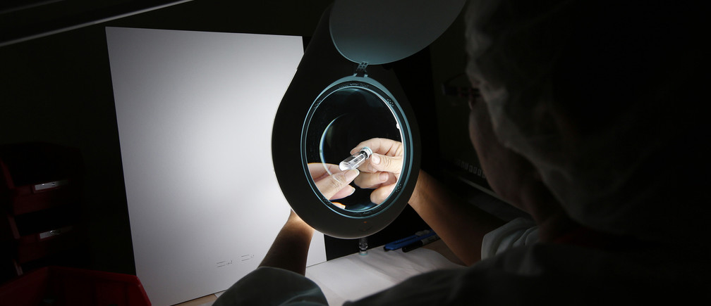 An employee checks a Sci-B-Vac, a hepatitis B vaccine, at SciVac's laboratory in the central Israeli city of Rehovot July 14, 2013.