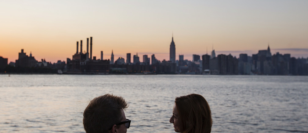 A couple laughs as they watch the sun set behind the skyline of New York, July 16, 2013. The National Weather Service issued heat advisories for dozens of northeastern cities and surrounding areas in Connecticut, Massachusetts, Rhode Island, upstate New York and Long Island. REUTERS/Lucas Jackson (UNITED STATES - Tags: ENVIRONMENT CITYSCAPE) - GM1E97H0PEY01
