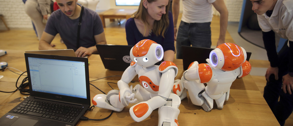 "Visitors and staff work on computers next to humanoid robots ""Nao"" in the developing space at the workshop of Aldebaran Robotics company during its opening week in Issy-Les-Moulineaux near Paris July 2, 2014. The Aldebaran Workshop opens three main spaces, discovering, learning and developing, for the public to interact with humanoid robots and to introduce a new generation of emotionally-savvy robots which organisers hope one day could become man's new best friend. Picture taken July 2, 2014.     REUTERS/Philippe Wojazer  (FRANCE - Tags: BUSINESS INDUSTRIAL) - PM1EA721A2J01"