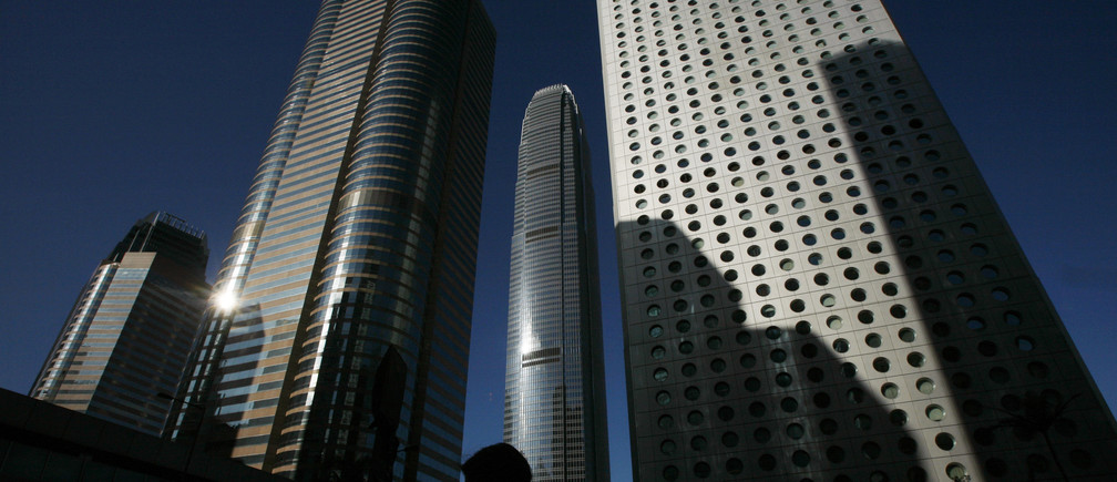 A man walks in front of skyscrapers at the financial Central district in Hong Kong February 25, 2009. Hong Kong's economy could shrink by 2-3 percent this year as it feels the impact of the global downturn, Financial Secretary John Tsang said on Wednesday in his annual budget, which offered few handouts to help people weather the downturn.    REUTERS/Bobby Yip   (CHINA) - GM1E52P1DJK01