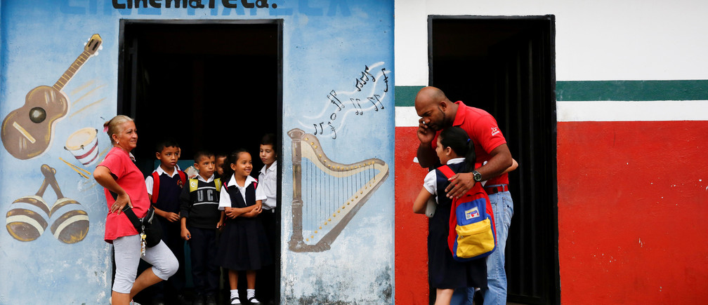 A girl arrives to an improvised classroom above a state-run supermarket, which is part of state school Monsenor Marco Tulio Ramirez Roa, in La Fria, Venezuela