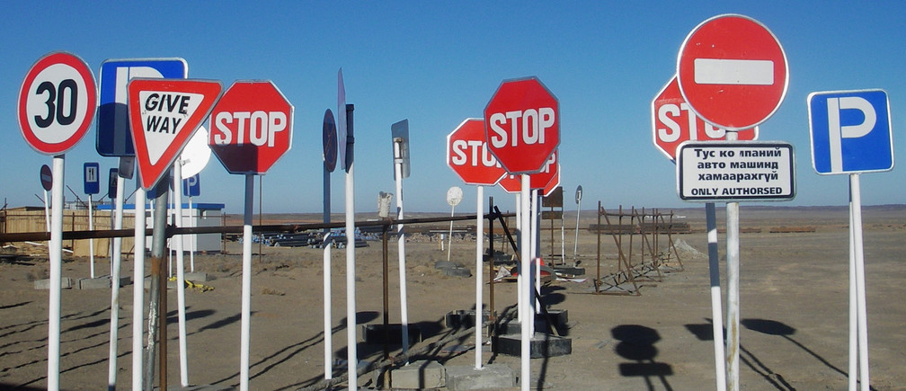 Road signs stand in Mongolia's South Gobi desert, awaiting to be deployed during the development of Oyu Tolgoi copper and gold mine in Mongolia November 10, 2007. Mining firms are telling Mongolia's parliament to unlock the country's mining sector by taking a landmark decision on a multi-billion dollar copper deal. Oyu Tolgoi's potential was enough to make geologists' eyes bulge on a recent tour of the site, where traditional Mongolian white tents stand alongside thousands of crates containing 720 km of drill core -- rock drilled out during the exploration phase. Picture taken November 10, 2007.   REUTERS/Tom Miles   (MONGOLIA) - RTXTXH