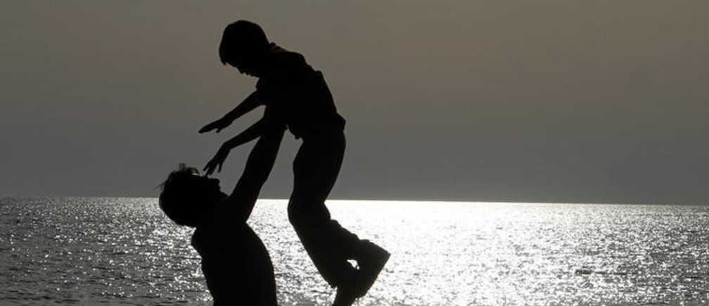 A father plays with his son on a beach facing the Adriatic sea, near the city of Durres, some 40 km (25 miles) from Tirana April 28, 2013.            REUTERS/Arben Celi (ALBANIA - Tags: SOCIETY)