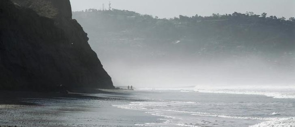 People walk next to the bluffs and mist along Torrey Pines State Beach in San Diego, California, January 24, 2011.  REUTERS/Mike Blake   (UNITED STATES - Tags: ENVIRONMENT)