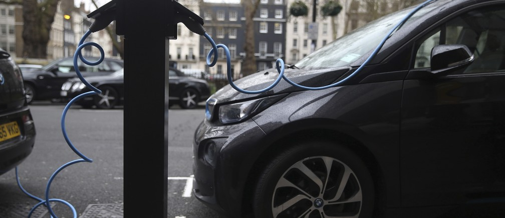 Electric cars are plugged into a charging point in London, Britain April 7, 2016.