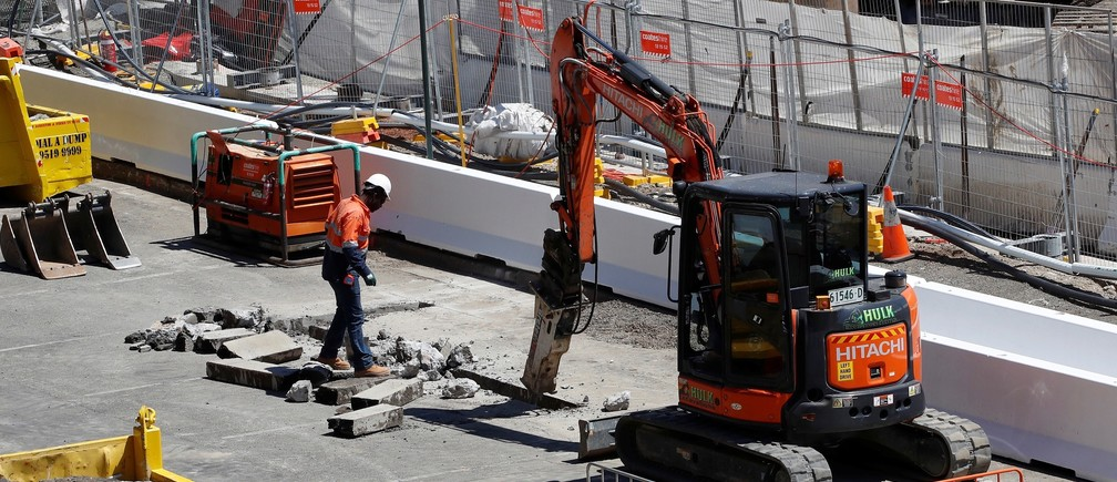 A worker looks on as a drill breaks the pavement on a construction site next to Barangaroo building complex in Sydney, Australia