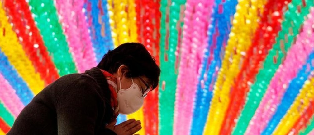 Buddhist believer wearing a face mask to prevent contracting the coronavirus disease (COVID-19) prays under colorful lanterns in preparation of the upcoming birthday of Buddha at a temple in Seoul, South Korea, March 25, 2020. REUTERS/Kim Hong-ji - RC2PQF9UGD0C