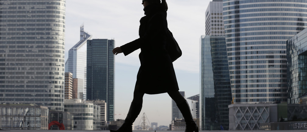A Businesswoman is silhouetted as she makes her way under the Arche de la Defense, in the financial district west of Paris.