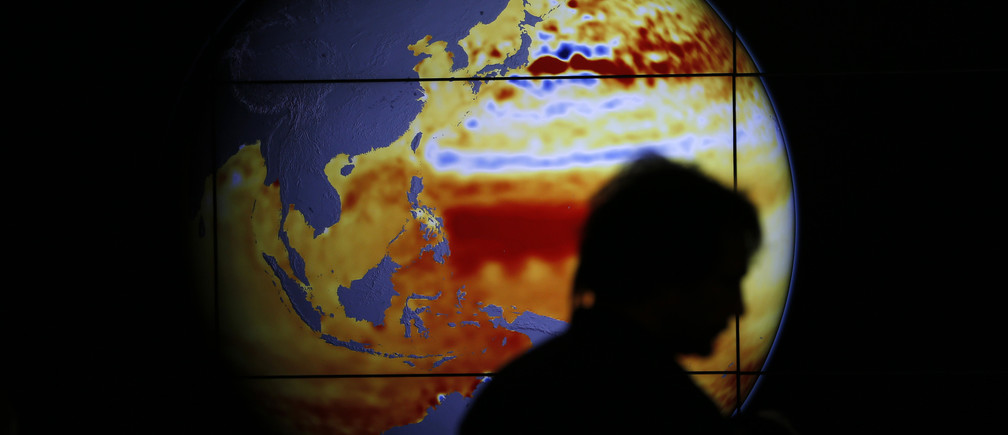 A woman walks past a map showing the elevation of the sea in the last 22 years during the World Climate Change Conference 2015 (COP21) at Le Bourget, near Paris, France, December 11, 2015.  REUTERS/Stephane Mahe  TPX IMAGES OF THE DAY  - LR1EBCB148RZ4