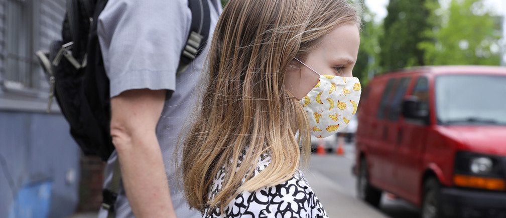 Lydia Hassebroek waits to cross the street with her father during the outbreak of the coronavirus disease (COVID-19) in Brooklyn, New York, U.S., May 22, 2020. REUTERS/Caitlin Ochs - RC23UG9PE75L