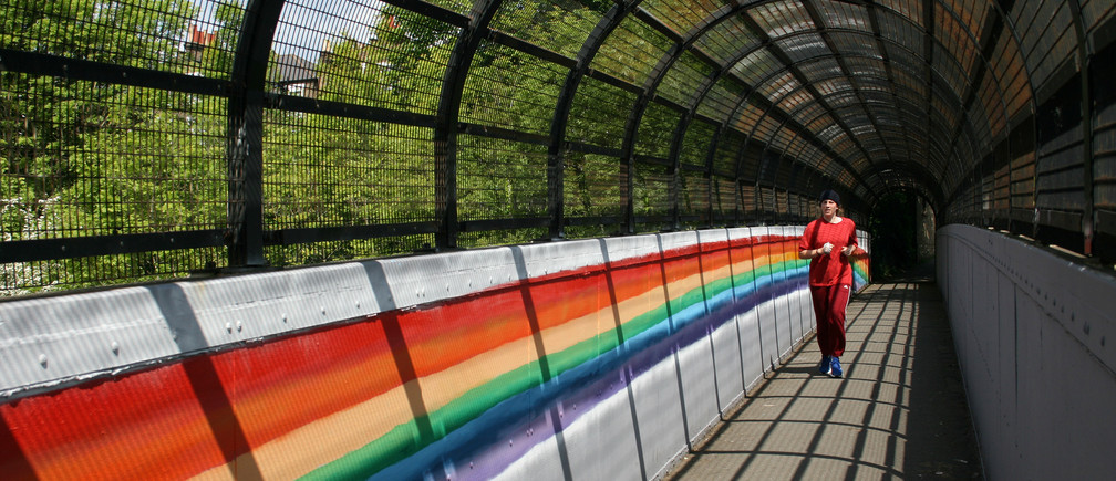 A woman runs past a mural of a rainbow in Brockley, following the outbreak of the coronavirus disease (COVID-19), London, Britain, May 4, 2020. REUTERS/Adam Oliver - RC2UHG95RUJV