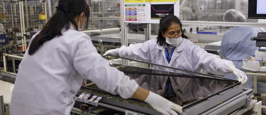 Women assemble an Aquos television at Sharp Corp's Tochigi plant in Yaita, north of Tokyo, November 19, 2015.