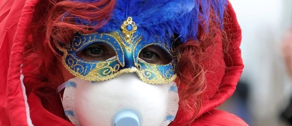 Masked carnival reveller wears protective face mask at Venice Carnival, which the last two days of, as well as Sunday night's festivities, have been cancelled because of an outbreak of coronavirus, in Venice, Italy February 23, 2020.  REUTERS/Manuel Silvestri     TPX IMAGES OF THE DAY - RC2E6F95HAOG