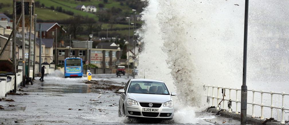 Waves crash against the coastal wall in the village of Carnlough  as high tides and strong winds cause some flooding in coastal areas of Northern Ireland January 3, 2014.  REUTERS/Cathal McNaughton  (NORTHERN IRELAND - Tags: ENVIRONMENT) - GM1EA131TKB02