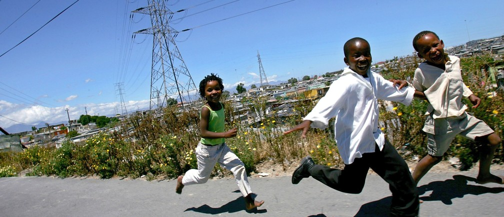 Children play beneath power lines in Khayelitsha township, near Cape Town November 15, 2005.