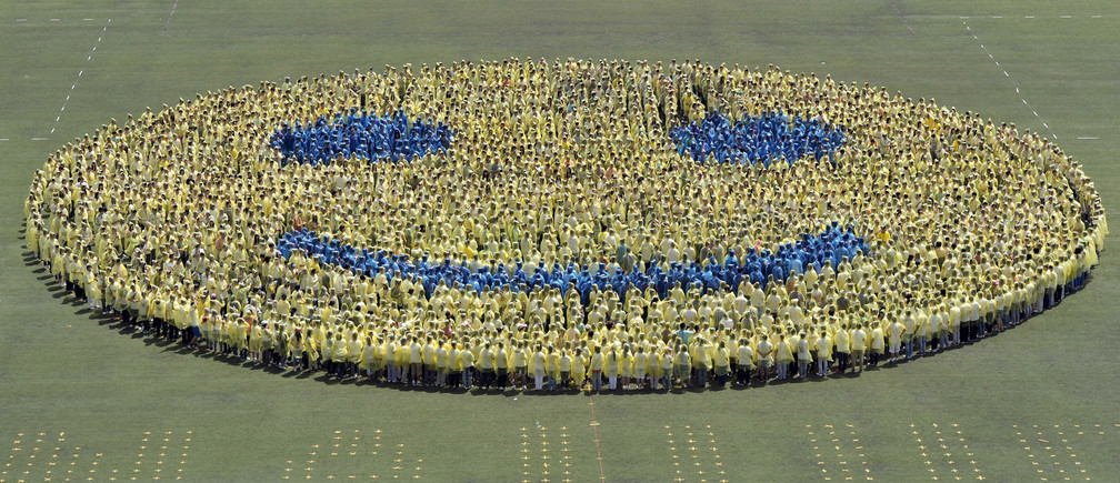 Students stand in formation on a field as they form a smiley face in an attempt to break a world record in celebration of the 110th anniversary of their university in Nanjing, Jiangsu province April 27, 2012. A total of 3,110 students from Nanjing Agricultural University broke the Guinness World Record for World Largest Smiley Face on Friday, overtaking the last world record of 2,961 volunteers in Canada on July 2011, local media reported. REUTERS/Sean Yong (CHINA - Tags: EDUCATION SOCIETY TPX IMAGES OF THE DAY) - GM1E84R17F001