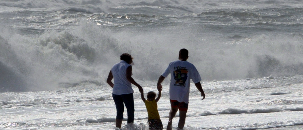 Parents carry their young son over surging waves that pound the coast ofSouth Nags Head on the Outer Banks of North Carolina, September 16, 2003 asHurricane Isabel approaches off the Atlantic coast. Hurricane Isabelweakened on Tuesday but thousands of people on the North Carolina coast wereurged to evacuate their homes as the storm threatened a large swath of theheavily populated U.S. eastern seaboard.  NO RIGHTS CLEARANCES OR PERMISSIONS ARE REQUIRED FOR THIS IMAGE  REUTERS/Jason ReedPP03090092JIR/GAC - RP4DRIFSIKAA