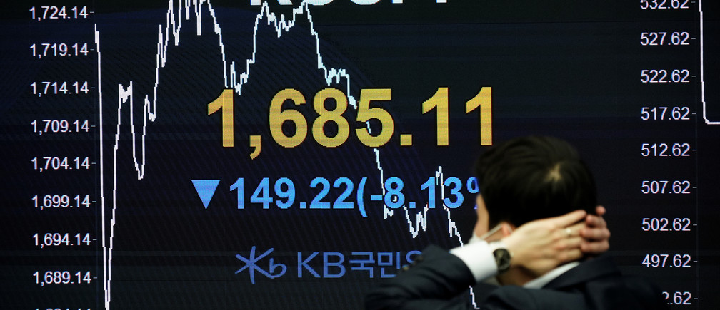 A currency dealer works in front of an electronic board showing the Korea Composite Stock Price Index (KOSPI) at a dealing room of a bank in Seoul, South Korea, March 13, 2020.   REUTERS/Kim Hong-Ji - RC2QIF9NGH47