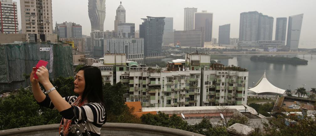 A woman takes a photo on Penha Hill, overlooking the Macau peninsula.