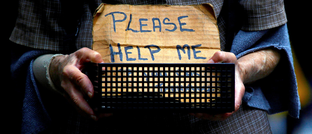 """A woman claiming to be homeless holds a container bearing a sign reading """"Please Help Me"""" as she begs for money on a footpath in central Sydney, Australia, October 28, 2016.    REUTERS/David Gray - S1AEUJMWJXAA"""