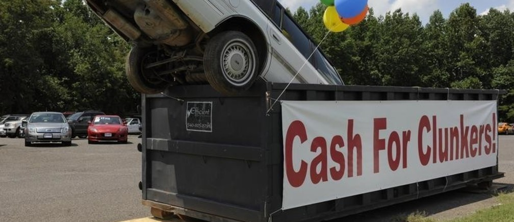 """An old car dropped in an industrial trash bin advertising the Cash for Clunkers program at Battlefield Ford in Culpeper, Virginia, August 1, 2009. Americans flocked to auto dealerships this month to take advantage of government rebates for gas-guzzling """"clunkers"""" and promptly drained the program's $1 billion in funding, leaving some prospective buyers in limbo.  REUTERS/Jonathan Ernst    (UNITED STATES TRANSPORT POLITICS BUSINESS IMAGES OF THE DAY) - GM1E5820AR701"""