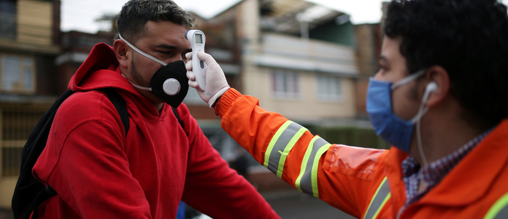 An employee of the construction company Amarilo, wearing a face mask, measures the body temperature of another employee, amid the coronavirus disease (COVID-19) outbreak in Bogota, Colombia May 19, 2020. Picture taken May 19, 2020.