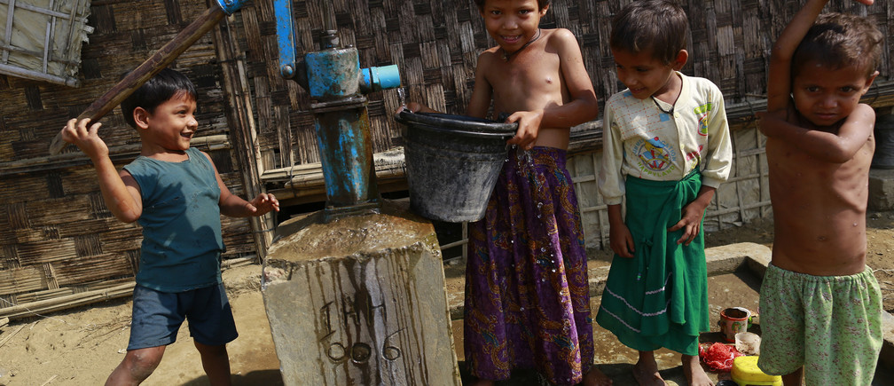 Rohingya children collect water at a refugee camp outside Sittwe, March 2014.