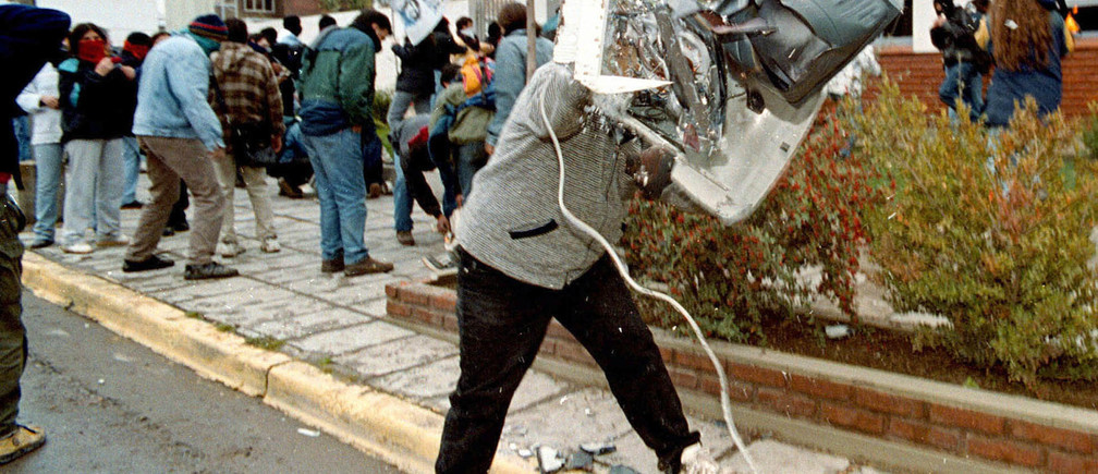 An angry striker smashes a computer which was looted from a branch of the Spanish oil company Repsol-YPF, in the southern Argentine province of Neuquen during a nationwide strike against the government of Fernando de la Rua on June 9. Workers around the country widely adhered to the strike called by labor unions to protest a recent austerity plan imposed to spark the ailing economy.EM/RCS - RTR554M