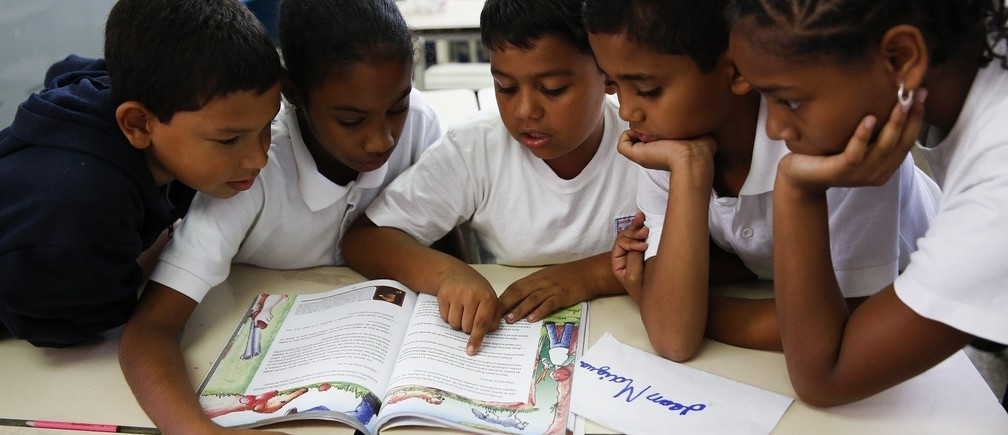 "Children read state-issued textbooks from the ""Bicentennial Collection"" at a classroom of the Eleazar Lopez Contreras school in Caracas May 23, 2014.  Venezuela's government has published dozens of new textbooks that glorify late president Hugo Chavez and belittle his adversaries, infuriating opposition critics who call them part of a campaign to indoctrinate school children. Originally introduced in mid-2011, the textbooks have become a hot-button issue again amid a broad state-run review of the education system that some fear could boost the ruling Socialist Party's imprint on classrooms. Picture taken on May 23, 2014. REUTERS/Carlos Garcia Rawlins (VENEZUELA - Tags: EDUCATION POLITICS) - RTR3RVIS"