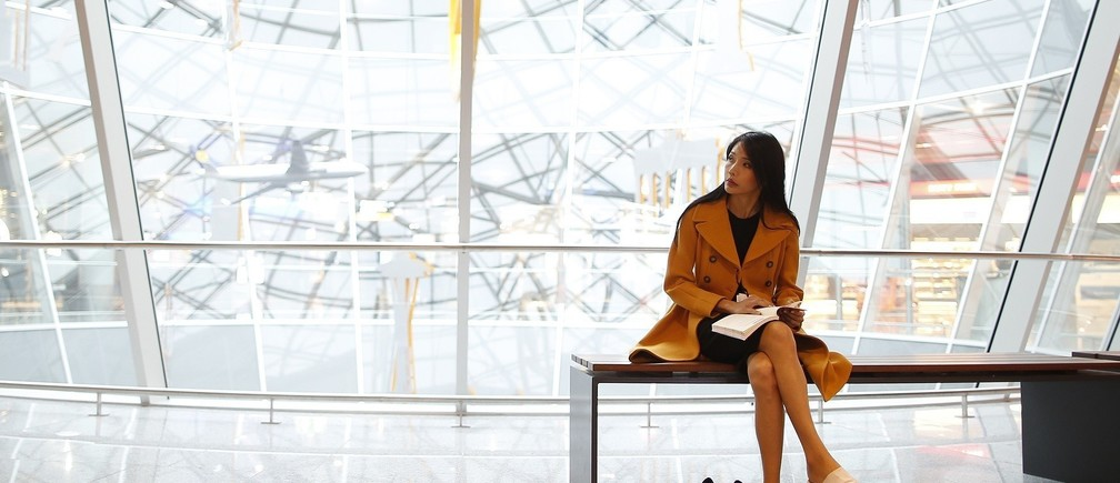A woman with a book sits on a bench at the departure area at the Fraport airport in Frankfurt November 14, 2012. Frankfurt airport's new Mandarin-speaking personal shopper service is just one example of how leisure and travel firms in crisis-struck Europe are trying to tap into the seemingly inexhaustible spending power of Chinese tourists. Value-added tax (VAT) refund data shows that Chinese travellers, who could overtake Germans as the world's biggest spenders on foreign travel this year, top the tax free shopping leaderboard in European cities like Paris, London and Frankfurt. Picture taken November14, 2012.