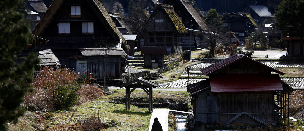 A visitor strolls near traditional Gassho style houses in Shirakawa-go (Shirakwa Village), one of Japan's UNESCO World Heritage sites, Gifu Prefecture, Japan December 2, 2017. Picture taken December 2, 2017.  REUTERS/Issei Kato - RC1B7D4E7330