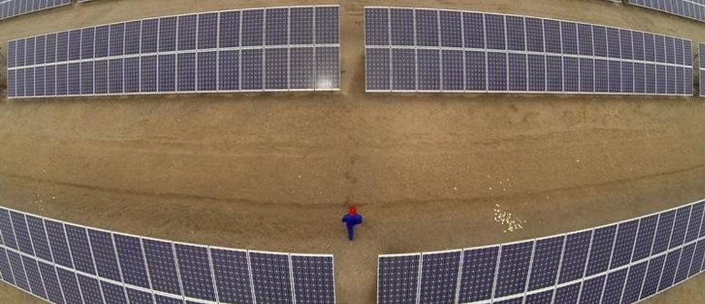 A worker inspects solar panels at a solar farm in Dunhuang, 950km (590 miles) northwest of Lanzhou, Gansu Province September 16, 2013. China's solar panel industry is showing signs of booming again after a prolonged downturn - raising fears of another bust when the splurge of public money that is driving a spike in demand dries up. Lured by generous power tariffs and financing support to promote renewable energy, Chinese firms are racing to develop multi-billion dollar solar generating projects in the Gobi desert and barren hills of China's vast north and northwest. Picture taken on September 16, 2013. REUTERS/Carlos Barria (CHINA - Tags: BUSINESS ENERGY)