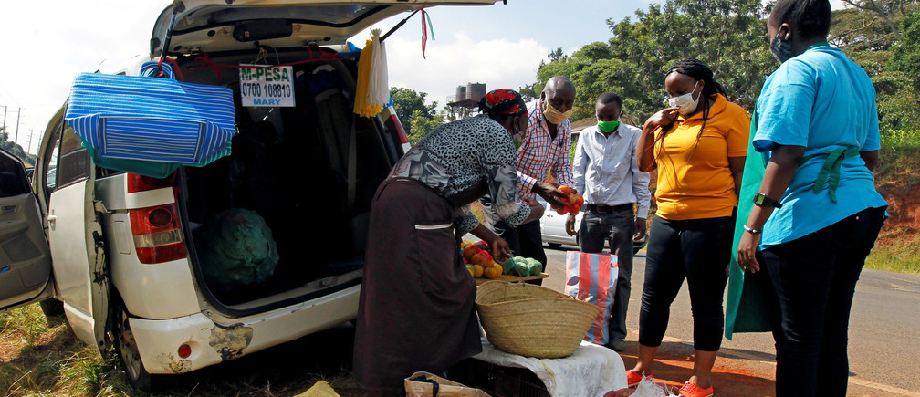 Motorists sell fruits and vegetables to customers next to their vehicle, used as an alternative mobile grocery stall, along the highway, following a lockdown due to the coronavirus disease (COVID-19) outbreak, on the outskirts of Nairobi, Kenya May 25, 2020. REUTERS/Njeri Mwangi - RC2OVG9SG2UP