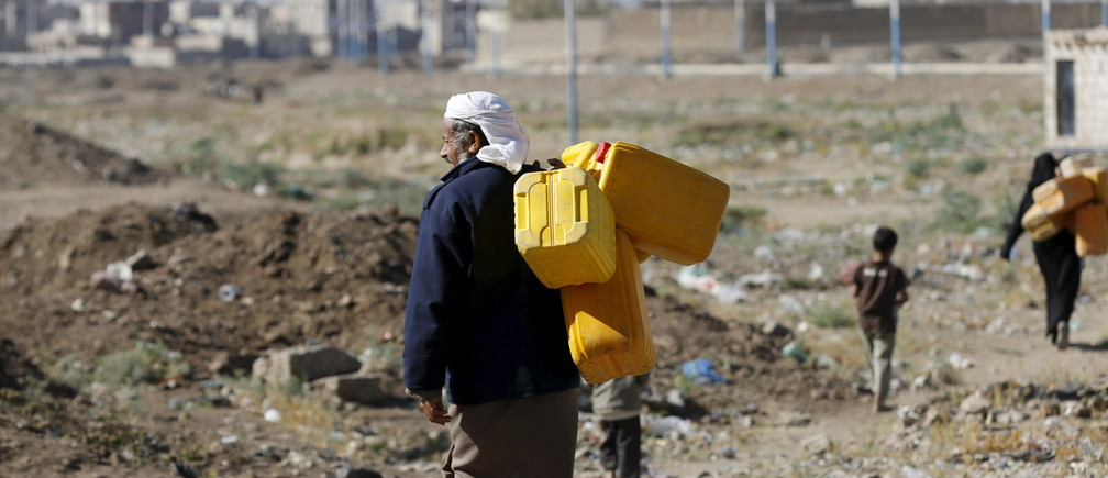 A man carries jerrycans to fill with water from a nearby water well, amid an acute shortage of water supplies in Yemen's capital Sanaa November 11, 2015. REUTERS/Khaled Abdullah - GF20000054843
