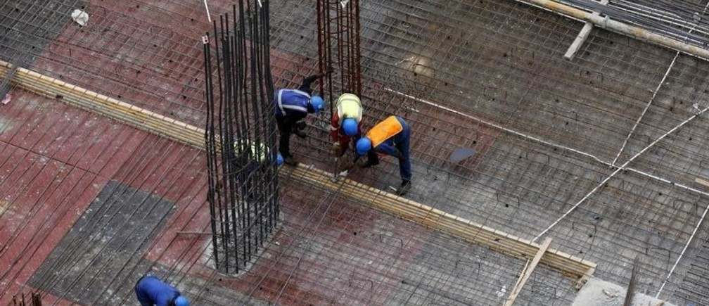 Labourers work on a construction site in Johannesburg's upmarket Sandton suburb, February 5, 2016. In many of Africa's big cities, including Lagos, Nairobi, Kinshasa and small pockets of Johannesburg, growth remains robust and investors are prospering in retail, technology, construction and healthcare sectors. Picture taken February 5, 2016. REUTERS/Mike Hutchings - GF10000300743