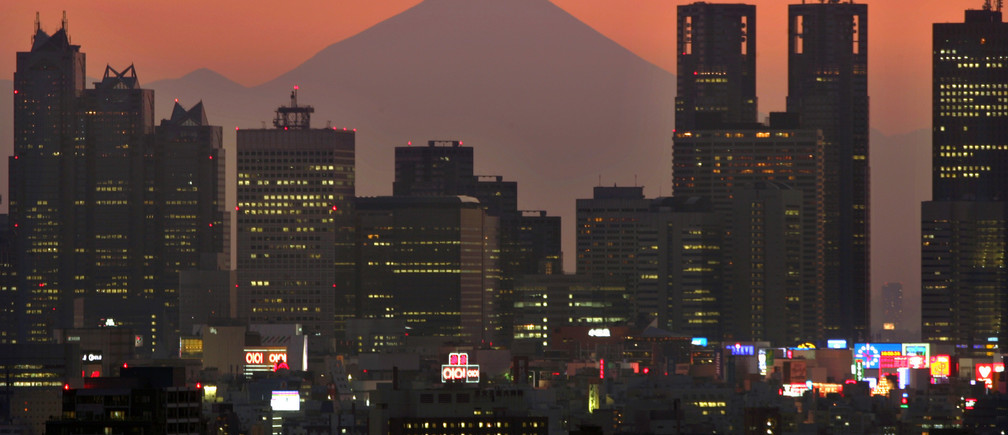 Japan's highest peak, Mt Fuji, stands tall over the skyscrapers of Tokyo's Shinjuku district in Tokyo November 27, 2004. The 3,776-metre peak is located in central Japan, about 110 km (68.75 miles) southwest of Tokyo. Photo taken November 27, 2004. REUTERS/Kimimasa Mayama  KM/FA - RP5DRHXWYYAC