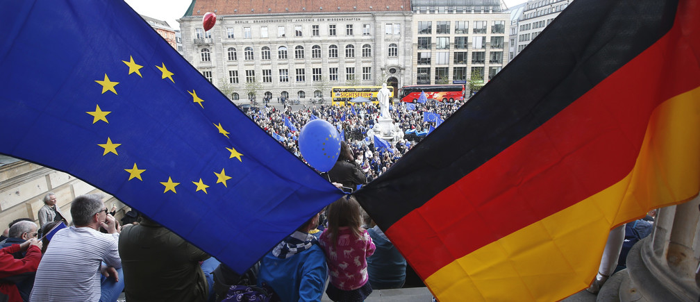 """Participants of the Pro-Europe """"Pulse of Europe"""" movement hold European Union and German flags during a protest at Gendarmenmarkt square in Berlin, Germany, April 2, 2017.      REUTERS/Fabrizio Bensch TPX IMAGES OF THE DAY - LR1ED4211DUIZ"""